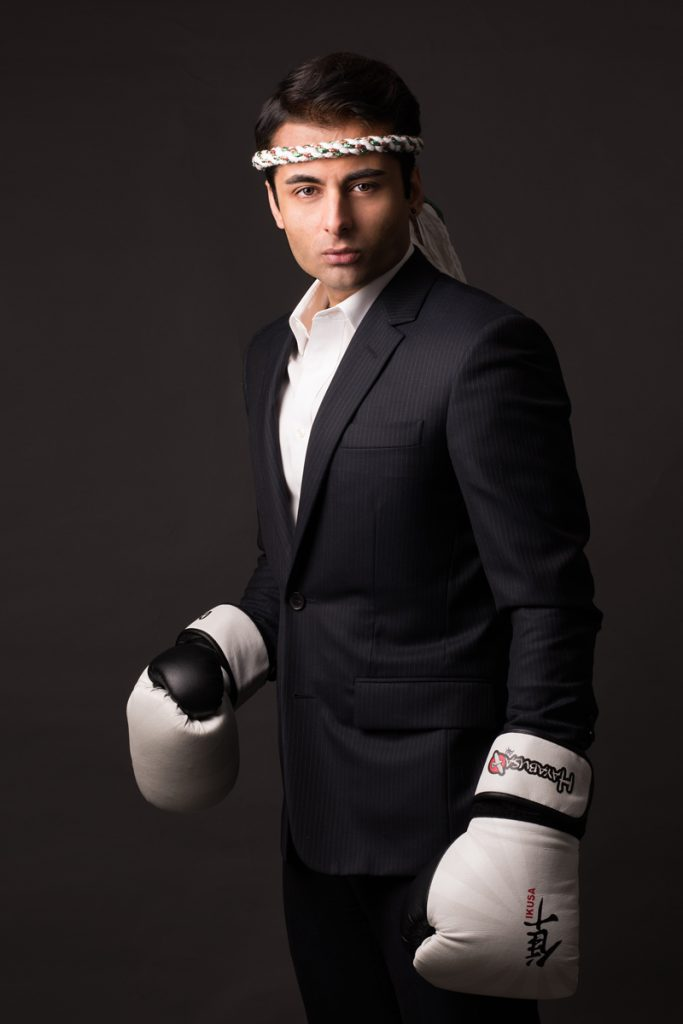 studio portrait of business man in suit with boxing gloves