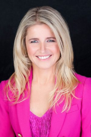 headshot of blonde women with pink jacket